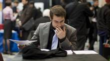 A job seeker fills out an application form at the Bi-lingual Job Fair and Training Expo in Toronto on Thursday March 8, 2012. (Chris Young For The Globe and Mail)