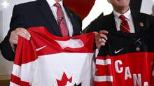 Tom Renney and Jim Hornell, chairman of the board, pose with jerseys (Jeff McIntosh/The Canadian Press)
