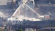 Fire fighters douse rail containers in downtown Lac-Mégantic, Que., early July 7, 2013. (Moe Doiron/The Globe and Mail)