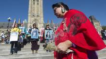 A woman burns sage during a rally for missing and murdered indigenous women on Parliament Hill in Ottawa on Oct. 4, 2016. (Adrian Wyld/THE CANADIAN PRESS)