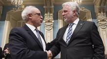 Quebec Premier Philippe Couillard shakes hand with Quebec Finance Minister Carlos Leitao moments before presenting the budget speech at the legislature in Quebec City, on March 28, 2017. (Jacques Boissinot/THE CANADIAN PRESS)