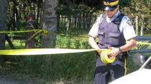 An RCMP officer puts up police tape near a rural residence south of Calgary, Friday, Aug. 10, 2012. A peace officer who attended the acreage near Priddis, Alta. was transported to hospital where he later died. (Bill Graveland/THE CANADIAN PRESS)