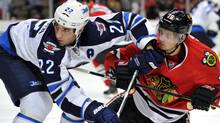 Winnipeg Jets right wing Chris Thorburn (22) checks Chicago Blackhawks center Marcus Kruger (16) during the third period at the United Center. The Hawks beat the Jets 4-3. Rob Grabowski-US PRESSWIRE (Rob Grabowski-US PRESSWIRE/Rob Grabowski)