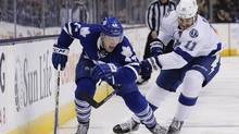 Toronto Maple Leafs' Morgan Rielly skates with the puck against the Tampa Bay Lighting's Brian Boyle during the second period of an NHL game in Toronto, Tuesday March 15, 2016. (Mark Blinch/THE CANADIAN PRESS)