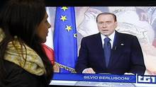 A woman watches former Italian prime minister Silvio Berlusconi on TV Sunday as he reads his farewell speech. (Alessandro Garofolo/Reuters/Alessandro Garofolo/Reuters)