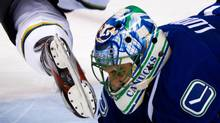Vancouver Canucks goalie Roberto Luongo is nearly hit in the mask by the skate of Dallas Stars' Adam Burish after he tripped over Luongo during the third period of an NHL game in Vancouver on March 6, 2012. (Darryl Dyck/The Canadian Press/Darryl Dyck/The Canadian Press)