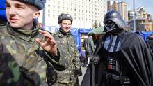 """""""Darth Vader"""", the leader of the Internet Party of Ukraine, talks with cadets during a rally in front of the Ukrainian Central Elections Commission in Kiev April 3. (© Shamil Zhumatov / Reuters/REUTERS)"""