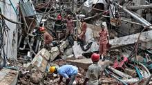 Bangladeshi firefighters and rescuers stand on the debris after a Monday evening boiler explosion at a garment factory owned by export-oriented Multifabs Ltd. at Kashimpur area in Gazipur district, outside capital Dhaka, Bangladesh, Tuesday, July 4, 2017. (A.M. Ahad/The Associated Press)