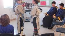 Grade 6 students at Iqaluit's Aqsarniit Middle School perform traditional throat singing via telepresence technology for a class, seen on the screen, in Busby, Alta., about 2,500 kilometres away. The new program, called Connected North, links remote northern classrooms with schools in the south, and transport scientists, astronauts, even Philadelphia's Museum of Art, via live video feed to the windswept shores of Frobisher Bay. (Genesee Keevil)