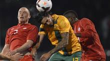 Australia's Rhys Williams, centre, rises above Canada's Iain Hume, left, and Tostaint Ricketts to head the ball during their international friendly soccer match at Craven Cottage in west London October 15, 2013. (TOBY MELVILLE/REUTERS)