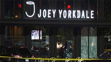 A police officer walks by a window with gunshot holes in it after shots were fired at a restaurant at the Yorkdale shopping mall in Toronto. (Mark Blinch/Reuters)
