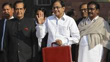 India's Finance Minister Palaniappan Chidambaram (centre) poses as he leaves his office to present the 2013/14 federal budget in New Delhi Feb. 28, 2013. (B MATHUR/REUTERS)