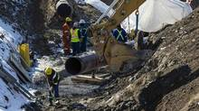 """The """"Line 9"""" Enbridge oil pipeline is seen being worked on in East Don Parkland in Toronto, March 6, 2014. The National Energy Board is set to make a decision on whether to allow Enbridge to reverse the flow of and increase the capacity of oil in a pipeline between southern Ontario to Montreal that has in operation for years. (MARK BLINCH/REUTERS)"""