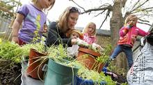 Patti Tinholt gardening in the back yard of her Toronto home with her four children on May 6, 2011. (Photo by Peter Power/The Globe and Mail) (Peter Power/Peter Power/The Globe and Mail)
