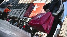 This file photo shows a shopper carrying Macy's bags while crossing an intersection outside Macy's in New York. (Bebeto Matthews/AP)
