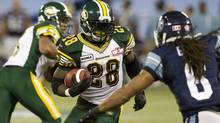 Edmonton Eskimos' Cory Boyd (centre) carries the ball as Toronto Argonauts' Marcus Ball (right) defends during first half CFL action in Toronto on Monday August 27 , 2012. (Chris Young/THE CANADIAN PRESS)