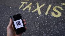 A photo illustration shows the Uber app logo displayed on a mobile telephone in this file photo. (TOBY MELVILLE)