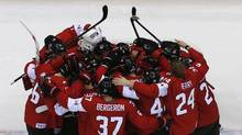 Canada's players huddle as they celebrate defeating Sweden in their men's ice hockey gold medal game at the Sochi 2014 Winter Olympics on Feb. 23, 2014. (MARK BLINCH/REUTERS)