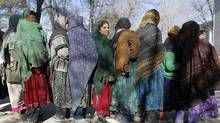Women wait in line to receive aid donated by the Turkish government in Kabul on March 5, 2012. (OMAR SOBHANI/REUTERS)