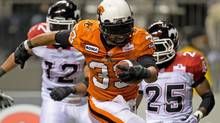 B.C. Lions' Andrew Harris, centre, rushes past Calgary Stampeders' Juwan Simpson, left, and Keon Raymond for a touchdown during the second half of a CFL game in Vancouver, B.C., on Saturday October 6, 2012. (DARRYL DYCK/THE CANADIAN PRESS)