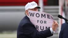 Republican presidential candidate Donald Trump holds a sign that reads, 'Women for Trump,' as he speaks during a campaign rally at the Lakeland Linder Regional Airport on Oct. 12, 2016, in Lakeland, Fla. (Joe Raedle/Getty Images)