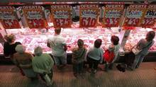Customers visit a butcher at a market in Barcelona in a file photo. Spain's economy shows no sign of recovery, the central bank governor said on Wednesday. (ALBERT GEA/REUTERS)