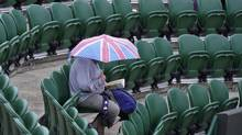 A spectator shelters under an umbrella at the Wimbledon Tennis Championships, in London, June 27, 2013. In contrast with previous economic downturns, the British economy today has a much less sheltered work force. (TOBY MELVILLE/REUTERS)