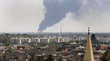 Black smoke billows over the skyline as a fire at the Tripoli airport oil depot rages out of control on July 28, 2014. The latest violence to plague Libya has so far killed scores of people and wounded hundreds as foreigners flee the chaos. (MOHAMMED BEN KHALIFA/ASSOCIATED PRESS)