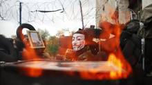 A pro-Russia protester wearing a Guy Fawkes mask sits on a barricade outside a regional government building in Donetsk, in eastern Ukraine, April 20, 2014. At least three people were killed in a gunfight in the early hours of Sunday near a Ukrainian city controlled by pro-Russian separatists, shaking an already fragile international accord that was designed to avert a wider conflict. (MARKO DJURICA/REUTERS)