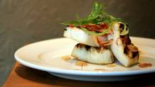 Neon squid at the Pourhouse is lightly grilled and simply dressed with garlic chips, scallions and chili. The delicate flavour and spongy texture are downright revelatory. (LAURA LEYSHON/LAURA LEYSHON/THE GLOBE AND MAIL)