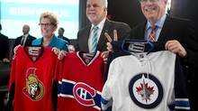 Ontario Premier Kathleen Wynne, from the left, Quebec Premier Philippe Couillard and Manitoba Premier Greg Selinger pose with sweaters of their province's teams that will participate in the NHL playoffs at the beginning of an interprovincial summit on climate change, Tuesday, April 14, 2015 in Quebec City. (Jacques Boissinot/THE CANADIAN PRESS)