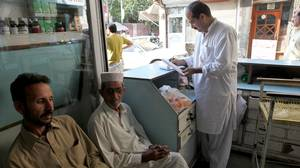 Ijaz Hussain (right, standing), a pharmacist in Peshawar, says he sells more psychiatric medication every day. Demand is fueled by the rising violence in Pakistan's tribal areas, he says, and shortages have pushed up the price of some antidepressants almost six times above usual rates. Psychiatrists say patients arrive from the tribal areas asking for sleeping pills to help them cope with the buzzing of U.S. Predator drones overhead.