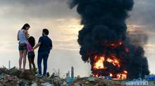 A family observes a fire after an explosion at a Venezuelan oil refinery in 2012. (Gil Montano/Reuters)