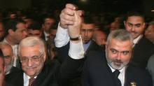 In this Saturday, March 17, 2007 file photo, Palestinian Authority President Mahmoud Abbas, left, and Prime Minister Ismail Haniyeh from Hamas, right, raise their linked arms as they move through the crowd at a special session of parliament in Gaza City. Palestinian officials from the rival Fatah and Hamas movements said Wednesday, April 27, 2011, they have reached an initial agreement on ending a four-year-old rift that has left them divided between rival governments in the West Bank and Gaza Strip. (Hatem Moussa/AP)