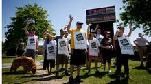 Striking teachers nd support staff who joined them on the picket line wave to a driver that showed support by honking their car horn outside Terry Fox Secondary School in Port Coquitlam, B.C., on Thursday, June 5, 2014 (Darryl Dyck for The Globe and Mail)