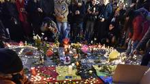 People put candles on painted hearts with the Belgian colors to mourn for the victims at the place de la Bourse in the center of Brussels, March 22, 2016. (Martin Meissner/AP)