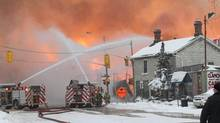 Firefighters battle a major fire in downtown Kingston, Ont., Tuesday, Dec.17, 2013. Ontario's Ministry of Labour has laid 22 charges in relation to a Kingston fire. (Lars Hagberg/The Canadian Press)