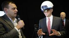 Ben Holfeld of Accenture's AI practice, left, helps Canadian Finance Minister Bill Morneau use a DAQRI Smart Helmet during the launch of the Vector Institute for AI at the MaRs Discovery District in Toronto on Thursday. (J.P. MOCZULSKI/The Canadian Press)