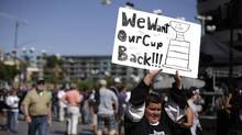 Adam Olguin, 11, holds up a sign for the Los Angeles Kings outside the Staples Center before the Kings' Game 1 of the NHL Stanley Cup Final hockey series against the New York Rangers on Wednesday, June 4, 2014, in Los Angeles. (Jae C. Hong/AP)
