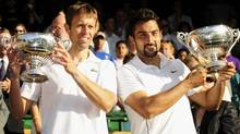 Daniel Nestor of Canada, left, and Nenad Zimonjic of Serbia hold their trophies after defeating Bob and Mike Bryan of the U.S. in their Men's Doubles finals match at the Wimbledon tennis championships in London, July 4, 2009 (Reuters)