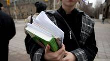 A University of Toronto student holds her textbooks at the corner of St. George Street and Harbord Street in Toronto on Wednesday, February 15, 2012. (Matthew Sherwood For The Globe and Mail)