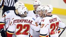 Calgary Flames' Dennis Wideman, second from right, celebrates his goal with teammates, left to right, Lee Stempniak, TJ Galiardi and Derek Smith, during second period split-squad NHL preseason action against the New York Islanders in Calgary, Alta., Tuesday, Sept. 17, 2013. (Jeff McIntosh/THE CANADIAN PRESS)