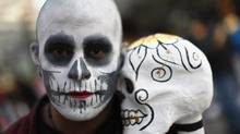 A man with a Calavera, or skull, painted on his face takes part in a Day of the Dead celebration in Mexico City, Nov. 1, 2011. Each year, Mexicans observe the holiday by gathering together to remember deceased relatives and friends. (Jorge Silva/REUTERS)