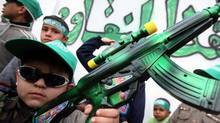 A Palestinian boy carries a toy gun spray painted green, the color of Hamas. (Heidi Levine for The Globe and Mail/Heidi Levine for The Globe and Mail)