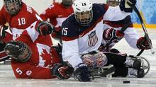 Canada's Kevin Rempel, middle, and Billy Bridges fight for the puck with Nikko Landeros of the U.S. during the semi-final sledge hockey game at the 2014 Sochi Winter Paralympic Games. The Canadians will play the United States this week at the inaugural Pan Pacific Championships in Buffalo, N.Y. (Alexander Demianchuk/Reuters)