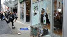 An G20 protester smashes a window at a downtown Toronto Starbucks. (Kevin Van Paassen/Kevin Van Paassen/The Globe and Mail)