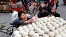 A vendor takes steamed buns for customers at a market in Xiangyang, Hubei province March 9, 2011.