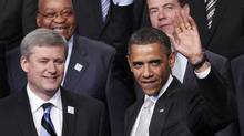 U.S. President Barack Obama waves as he stands with Canadian Prime Minister Stephen Harper (L), South African President Jacob Zuma and Russian President Dimitry Medvedev (back R) during a group photo at the G20 Summit in Toronto June 27, 2010. (CHRIS WATTIE/REUTERS/Chris Wattie)