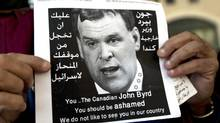 """A Palestinian protester holds a poster with a photo of Canadian Foreign Minister John Baird that reads in Arabic, """"You should be ashamed of your biased position towards Israel,"""" during Baird's meeting with Palestinian Foreign Minister Riad Malki, in front of the Palestinian foreign ministry in the West Bank city of Ramallah on Jan. 18. (Nasser Nasser/AP)"""