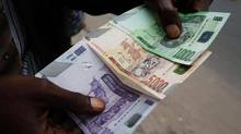 A trader displays new Congolese currency bills in the Democratic Republic of the Congo's capital, Kinshasa. The high-denomination notes remind some people of the old Zairean currency during the turbulent years of the country's economic history. (STAFF/REUTERS)